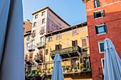 Alte Häuser an der Piazza delle Erbe mit Sonnenschirmen der Marktstände, Verona, Venetien, Italien