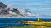 tiny orange lighthouse at the eastfjords of Iceland