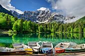 Bunte Booten liegen im Lago Fusine, Mangart im Hintergrund, Lago Fusine, Weißenfelser See, Julische Alpen, Friaul, Italien