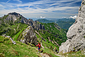Woman hiking from Grignone towards Grignetta, Grigna, Bergamasque Alps, Lombardy, Italy
