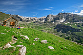 Woman hiking sitting at hut rifugio Stroppia, hut rifugio Stroppia, Val Maira, Cottian Alps, Piedmont, Italy