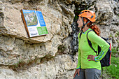 Woman reading sign of fixed rope route, Ferrata di Camoglieres, Val Maira, Cottian Alps, Piedmont, Italy