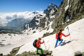 Man and woman hiking at Giro di Monviso ascending through snow, Monviso in background, Giro di Monviso, Monte Viso, Monviso, valley valle di Po, Cottian Alps, Piedmont, Italy