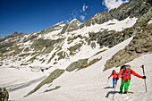 Man and woman hiking ascending through snow at Giro di Monviso, Giro di Monviso, Monte Viso, Monviso, Cottian Alps, France