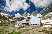Man and woman sitting at hut rifugio Vallanta, hut rifugio Vallanta, Giro di Monviso, Monte Viso, Monviso, Cottian Alps, Piedmont, Italy