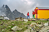 Man and woman hiking standing in front of bivouac, Giro di Monviso, Monte Viso, Monviso, Cottian Alps, Piedmont, Italy