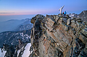 Two persons hiking standing at dawn at summit of Viso Mozzo, Viso Mozzo, Giro di Monviso, Monte Viso, Monviso, Cottian Alps, Piedmont, Italy