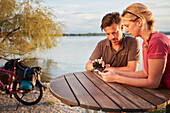 Young  couple using mobile phone on  a break on bicycle tour, Ambach, bavaria, germany