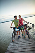 couple with Bikes on a jetty during bicycle tour, Ambach, bavaria, germany