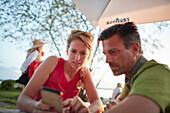 Paar nutzen Handy bei  Pause  auf Fahrradtour, Ambach, Bayern, Deutschland