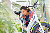 young woman mounts Battery to an eBike, Muensing, bavaria, germany