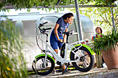 young woman fills air in a tire of an an eBike in front of an airstream trailer, Muensing, bavaria, germany