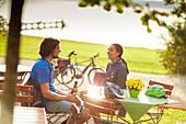 junge Frau und junger Mann  auf Fahrradtour,machen Pause im Biergarten, Münsing, Starnberger See, Bayern, Deutschland