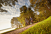 Young  woman on touring bike, young man on touring eBike on tour at lakeside, lake Starnberg, bavaria, germany