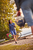 Young  woman withe helmet walks towards a man on lakeshore, lake Starnberg, bavaria, germany