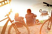 junge Frau  und junger Mann Paar sitzen mit Fahrrädern am Seeufer, Starnberger See, Bayern, Deutschland