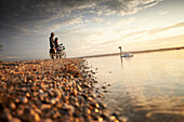 Young  woman on touring bike, young man on touring eBike on tour, lakeshore, Muensing, lake starnberg, bavaria, germany