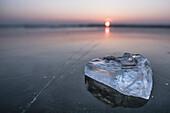Eisstück auf einem Gefrorenen See im Winter zur blauen Stunde
