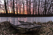 Boat frozen in ice in a river in the Spreewald at the blue hour at dawn