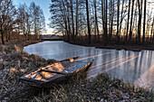 Im Eis eingefrorener Kahn in einem Fluss des Spreewaldes zur blauen Stunde im Morgengrauen