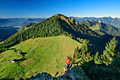 Woman hiking ascending on ridge towards Karkopf, alpine huts and Feichteck in background, Karkopf, Chiemgau Alps, Upper Bavaria, Bavaria, Germany