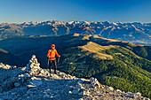 Man hiking ascending towards Peitlerkofel, Zillertal Alps in background, Peitlerkofel, Dolomites, UNESCO World Heritage Site Dolomites, South Tyrol, Italy