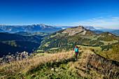 Woman hiking ascending towards Regenspitz, Berchtesgaden Alps and Schmittenstein in background, from Regenspitz, Salzkammergut, Salzburg, Austria