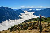 Frau beim Wandern blickt auf Nebelstimmung über dem Achensee, Rofan und Karwendel im Hintergrund, Seebergspitze, Karwendel, Tirol, Österreich