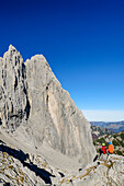 Man and woman sitting at Ellmauer Tor and looking towards Christaturm and Fleischbank, Ellmauer Tor, Wilder Kaiser, Kaiser range, Tyrol, Austria