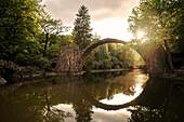 Rakotzbrücke im Gegenlicht der untergeheneden Sonne, Azaleen und Rhododendron Park Kromlau, Gablenz, Landkreis Görlitz, Sachsen, Deutschland