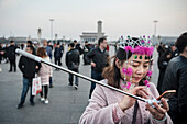 chinese woman with selfie stick and pink jewellery using mobile phone,  waiting for flag ceremony and  changing of the Guards at Tiananmen Square, Beijing, China, Asia