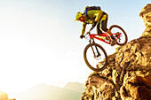 Middle aged man drops a steep rock clif on his mountainbike, Kitzbühel Alps, Tyrol, Austria