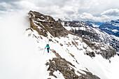 Junge Frau steigt im Winter mit Ski am Rucksack an einem Grat auf, Wolkenstimmung, Birkkarspitze, Karwendel, Tirol, Österreich