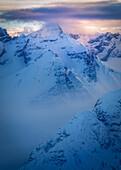 Farbintensiver Sonnenuntergang mit Nebelstimmung an markantem Berg, Wolkenmeer, Stubaier Alpen, Tirol, Österreich