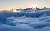 Sonnenaufgang über dem Wolkenmeer, Hütte auf Hügel  steht über den Wolken, Brenner Berge, Stubaier Alpen, Tirol, Österreich