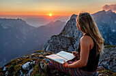 Young woman at the summit, writing into a book, Scheffauer, Wilder Kaiser, Tyrol, Austria