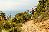 Young woman riding her mountainbike on a singletrail above the ocean, Finale Ligure, Italy