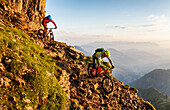 Two middle aged men ride down a rocky and steep hiking path on their mountainbikes, morning light, Wilder Kaiser mountain range in the background, Kirchberg, Tyrol, Austria