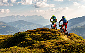 Two mountainbikers are riding over an overgrown hill in the Kitzbühel Alps, mountain range Wilder Kaiser in the background, Kirchberg, Tyrol, Austria