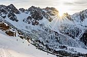 Gruppe Skitourengeher im Aufstieg mit Fellen durch Berghang im letzten Tageslicht, Scharnitz, Tirol, Österreich