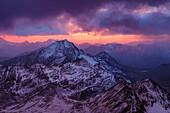 Eindrucksvoller Sonnenuntergang über eingeschneiten Berge, Sturm, Blick von der Biwakschachtel am Piz Tresero, Valfurva, Lombardei, Südtirol, Italien