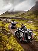 Zwei Geländewägen auf einer Schotterstraße vor wolkenverhangenen Bergen auf den Faröer Inseln