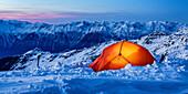 Orangfarbenes, leuchtendes Zelt im Schnee auf Gipfelhöhe bei Dämmerung, Innsbruck, Tirol, Österreich