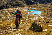 Young woman rides her mountainbike on a singletrail, direction of a turquoise blue mountain lake, Bormio, Lombardia, South Tyrol, Italy