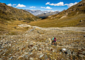Young woman rides a mountainbike through a high alpine valley with clear blue sky, Bormio, Lombardia, Italy