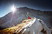 Ein Bergwanderer, Pause auf dem Weg zum Gipfel des Daniel , Daniel, Ammergauer Alpen, Tirol, Österreich