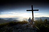2 Männer am Gipfelkreuz auf dem Gipfel des Petersköpfl, Inntal im Hintergrund , Vorderkaiserfelden, Zahmer Kaiser, Kaisergebirge, Tirol, Österreich