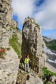 Woman hiking between rock spires towards Hoher Ifen, Hoher Ifen, Allgaeu Alps, valley of Walsertal, Vorarlberg, Austria
