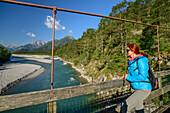 Frau steht auf Hängebrücke und blickt auf Lech und Lechtal mit Lechtaler und Allgäuer Alpen, Lechweg, Forchach, Lechtal, Tirol, Österreich