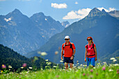 Man and woman hiking on Lechweg through meadow with flowers, Lechtal Alps in background, Weissenbach, Lechweg, valley of Lech, Tyrol, Austria
